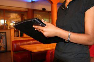 Digitale Speisekarte als Tablet-PC wird durch Kellner gebracht