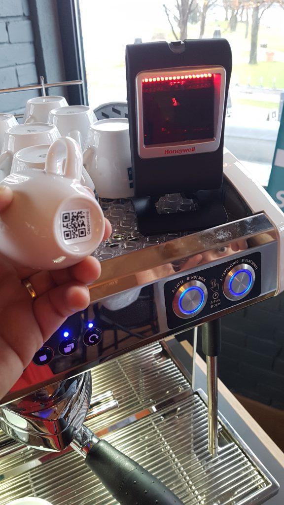 Digitale Kaffeetasse mit QR-Code unterhalb der Tasse. Scanner an Kaffeemaschine zum Erfassen der produzierten Artikel.